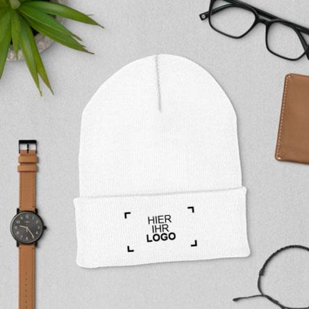 Lifestyle-Muster einer bestickten und individuell gestalteten Wintermütze, flach liegend, umgeben von einer Uhr und einer Brieftasche