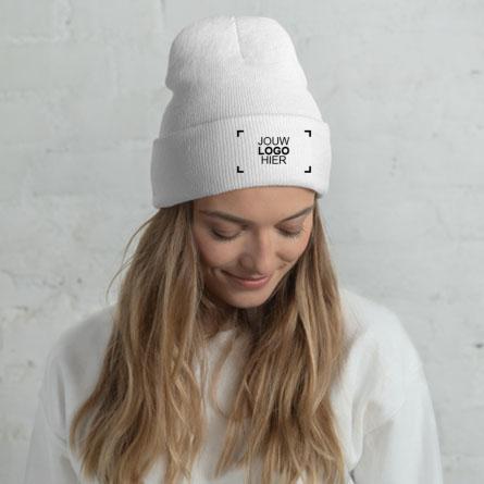 Vrouwelijk model met geborduurde gepersonaliseerde wintermuts met een voorbeeld van een logo-ontwerp