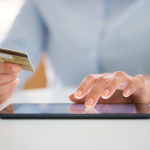 woman using credit card and tablet