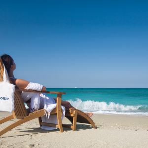 woman sitting in chair at the beach with custom tote bag
