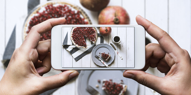 person taking picture of food with smartphone