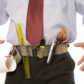 Man with an office supply tool belt marker coffee mug ruler scissors