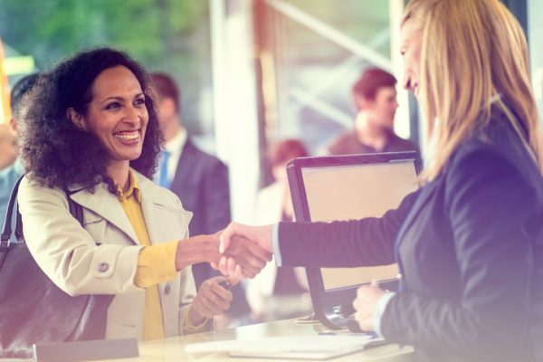 Woman at tradeshow shaking hands with a presenter