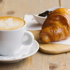 Latte and croissant on table