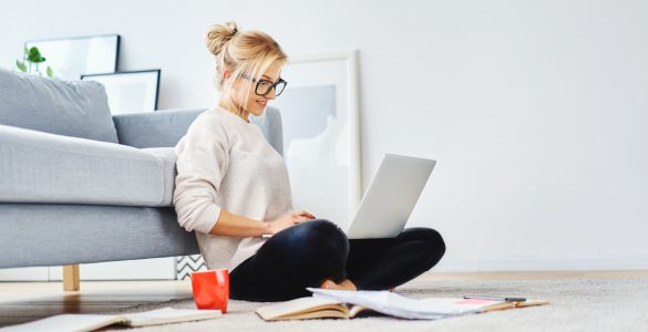 female looking at laptop searching for logo designs sitting on the floor of apartment