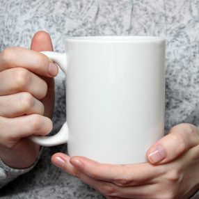 girl holding white coffee mug