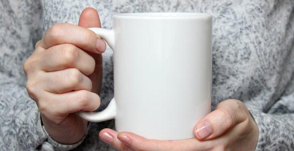 girl holding white coffee mug