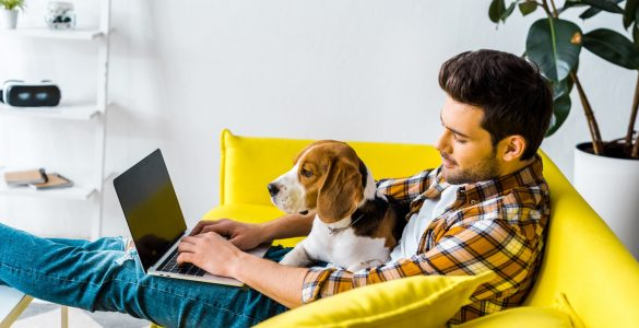 Man sitting on couch working on computer