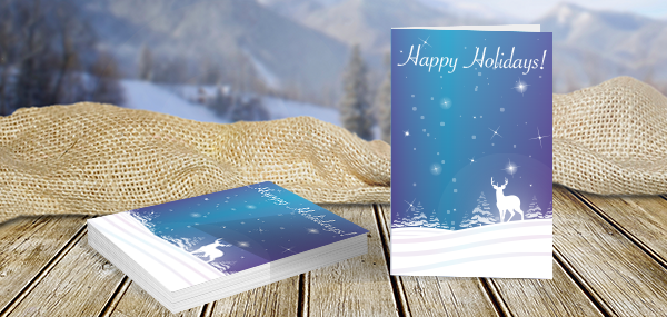 Stack of folded holiday cards with blue snow landscape design