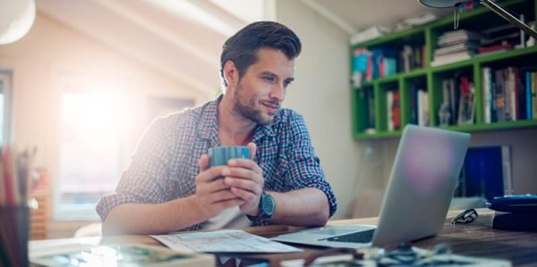 man sitting at desk looking at his laptop
