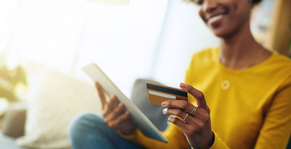 Woman looking at tablet with credit card in hand paying for item