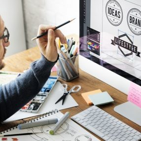 Designer on the computer using brand guidelines to create an on-brand logo for a company