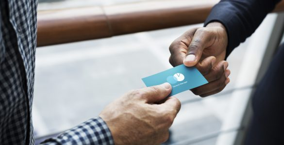 Two people trading business cards
