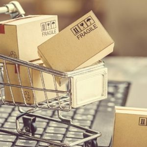 mini shopping card with packages on laptop