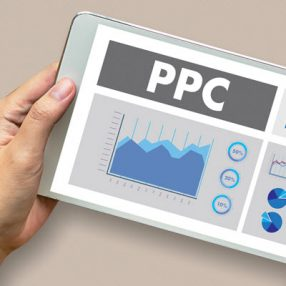 person holding tablet looking at PPC traffic