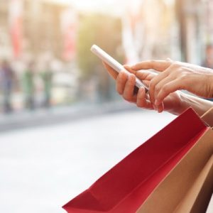 woman on her cell phone holding shopping bags